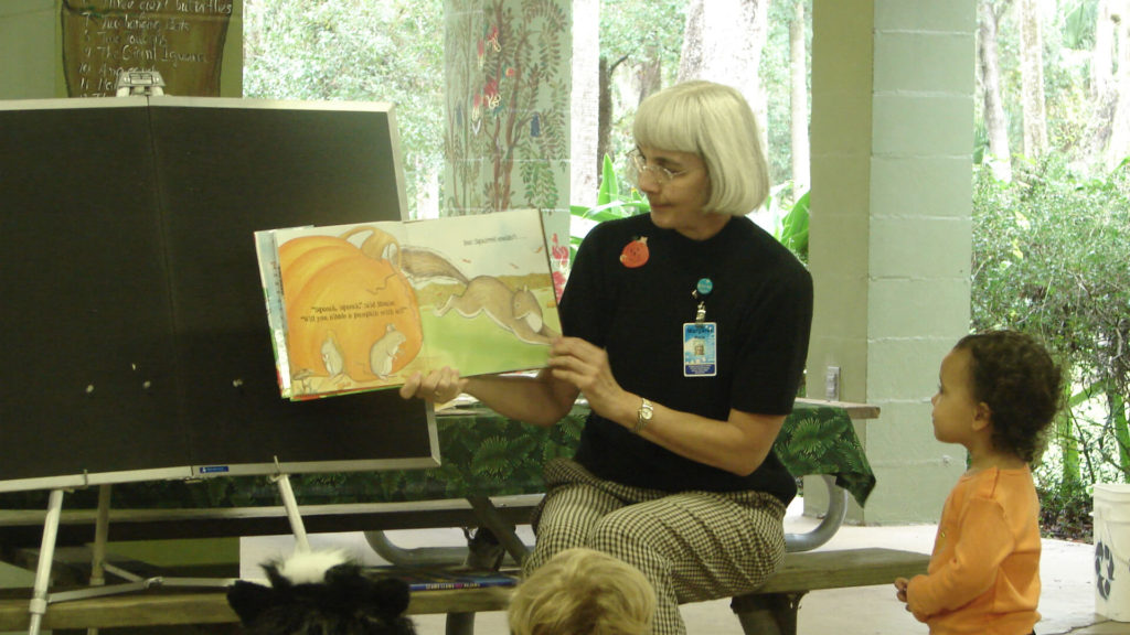 A woman reads to a group of children during Storytime at the Zoo