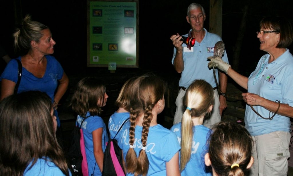Two guides explaining to some children about a bird